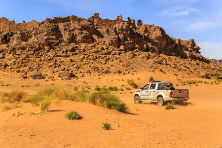 Merzouga, Morocco - February 26 2016: SUV driving beneath a rocky hill in the Moroccan desert on a sunny day Editorial