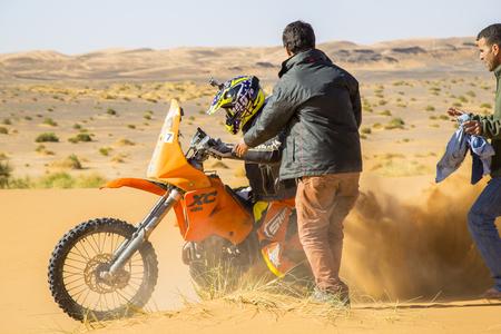 Merzouga, Marokko - 25. Februar 2016: Ein Motorradfahrer wirbelt Sand auf, während er versucht, sein orange Fahrrad in Sahara Desert in Gang zu bringen. Zwei Männer kommen ihm zu Hilfe. In der Ferne sieht man raueres Gelände; Sand mit Grasbüscheln und Hügeln Editorial