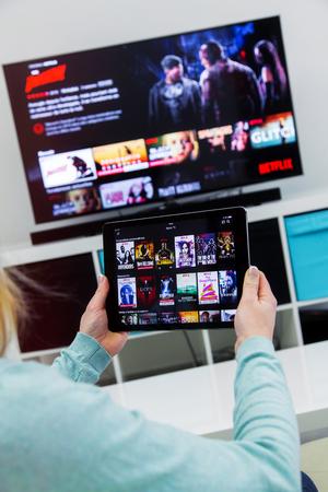 ベノン、フランス - 1月 21, 2018: フランスのNetflixホームページ上のタッチパッドを保持し、チャンネルを切り替える女性.テレビを背景に設定します。Netflix Inc.は1997年に設立されたアメリカの多国籍エンターテイメント企業です。