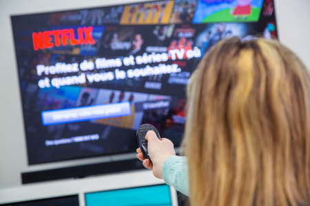 Benon, France - January 21, 2018: Woman Holding a TV remote control and switching channels on France Netflix HomePage. Netflix Inc. is an American multinational entertainment company founded on 1997