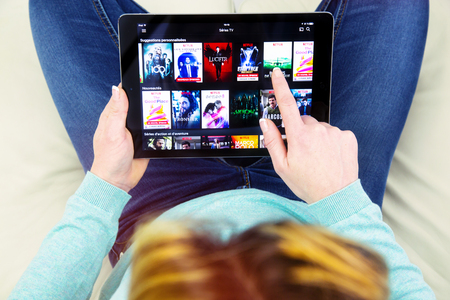 Benon, France - January 21, 2018: woman sitting cross-legged on her couch and using her touch pad to watch movies on demand on Netflix. Netflix Inc. is an American multinational entertainment company founded on 1997 에디토리얼