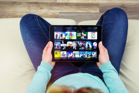 Benon, France - January 21, 2018: woman sitting cross-legged on her couch and using her touch pad to connect to watch films on the Amazon prime video app. Amazon prime video is a new online streaming video service created by the Amazon company.