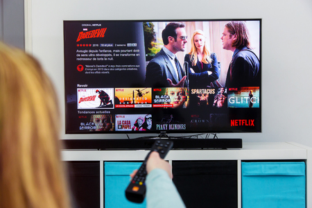 Benon, France - January 21, 2018: Woman Holding a TV remote control and play Dardevil, a Marvel film that is an original creation of Netflix industry. Netflix Inc. is an American multinational entertainment company founded on 1997