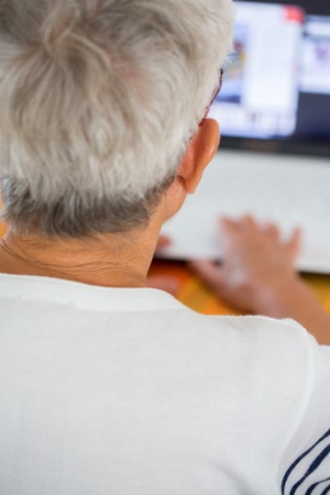 An old person with a pair of glasses in front of a laptop screen