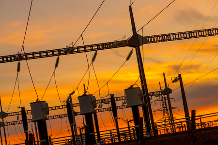 High voltage wire electrical energy plant producing electricity at sunset Stock Photo