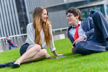 Young businessman and businesswoman sitting on the grass during a break