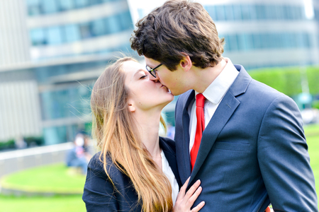 A couple of young executives about to kiss, illustrating the love relationships at work Stock Photo