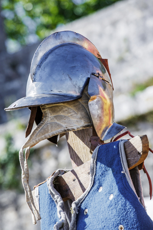 close up on a medieval helmet and plastron on a green background Stock Photo