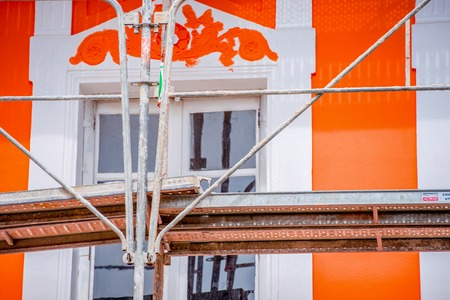 close up on a painters scaffold with a beautiful orange house in the background Stock Photo