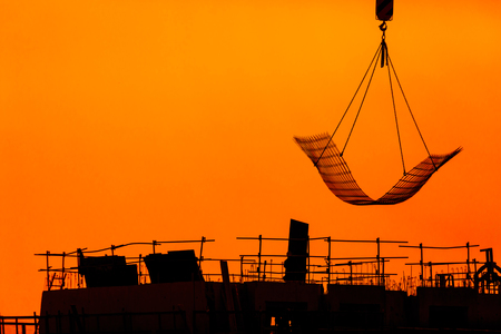 building workers working on a building under a beautiful sunset. Chinese shadow effect. Stock Photo