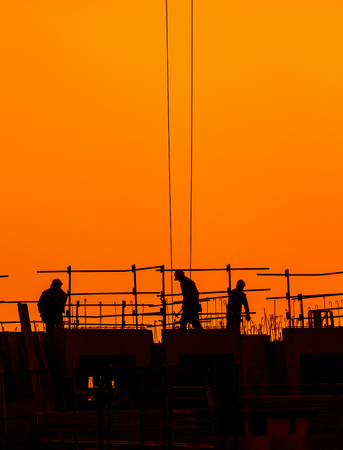 building workers working on a building under a beautiful sunset. Chinese shadow effect. Banque d'images