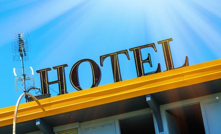 closeup on hotel sign board on building against blue sky 版權商用圖片
