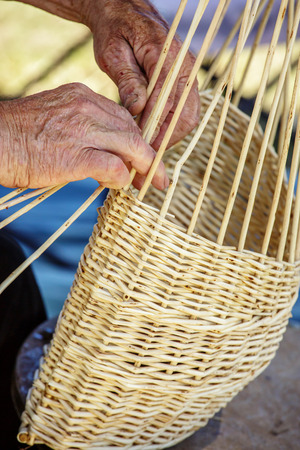 Closeup of man hand making a wicker can bamboo basket