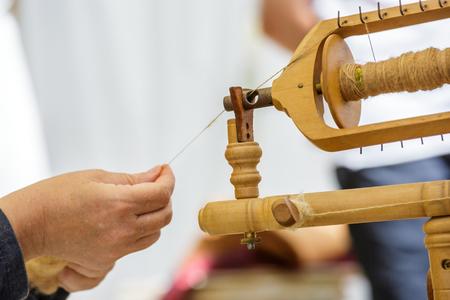 Nahaufnahme der Hand der alten Frau mit einem alten Spinnrad , um Wolle in Garn zu nähen