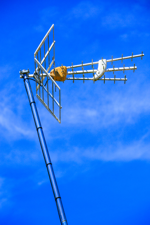 Television antenna standing tall against cloudy blue sky