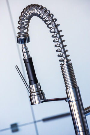 Slanted closeup view of shiny industrial design spray style kitchen faucet.