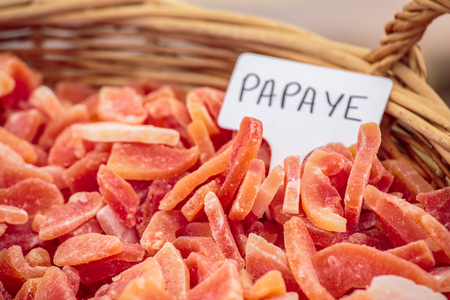 View of Basket of vivid candied fruit and a closeup of sign - Papaya (Papaye in French). Stock Photo