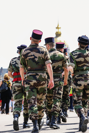 Rear view of a group of French soldiers in camouflage dress walking patrol.