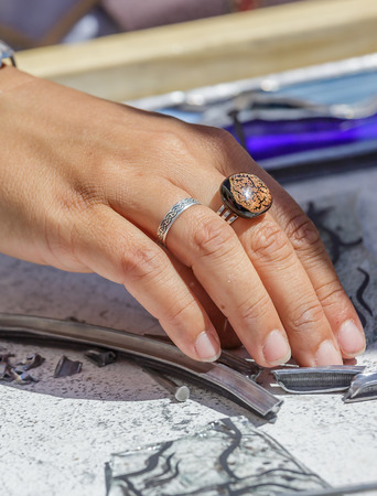 Brouage, France - June 25, 2016 : Closeup of woman artist hand manufacturing and working with stain glass during day at Brouage, France.