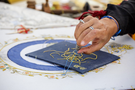 Brouage, France - June 25, 2016 : Closeup of female dressmakers hands doing embrodery work on blue white fabric at Brouage, France. Editorial