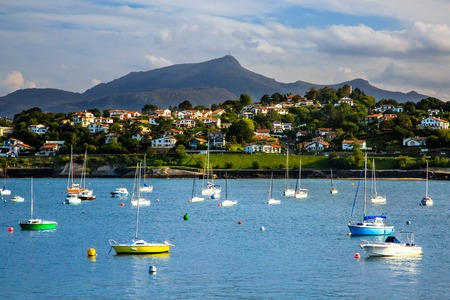 Saint Jean de Luz, France - September 26, 2016: saint jean de luz bay, with several boats on the sea and mountains ans resorts in the background. Its typical village on the edge of the atlantic in the region of the french Basque country,