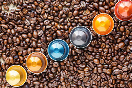 Coloreful Capsules of Coffee placed on a bed of coffee beans