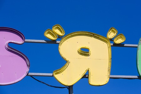Puilboreau, France - August 7, 2016 : Closeup on R letter of Toys R Us signboard on shop written in colorful alphabets against clear sky at Puilboreau, France