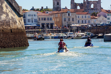 Ile de re, France - August 22, 2016 : Rear view of young tourists returning from a walk at sea and returning to the port of St. Martin with their jet ski. There are several boats and old buildings in the background Editorial