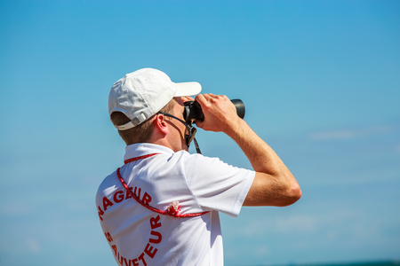 La tranche sur mer, France - July 31, 2016 : Lifeguard swimmer, called as Nageur sauveteur in French, watching sea through binoculars on duty at beach at La tranche sur mer, France.