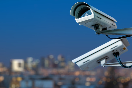 Focus on security CCTV camera monitoring system with panoramic view of a city on blurry background Archivio Fotografico