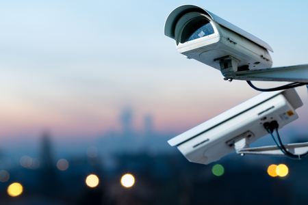 Focus on security CCTV camera monitoring system with panoramic view of a city on blurry background Banque d'images