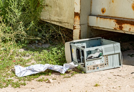 Cognac, France - August 16, 2012: old abandoned computer CPU on the floor near a container in a garbage