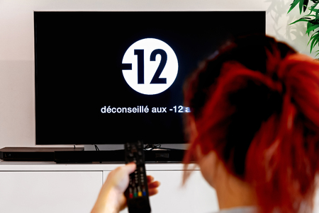 Woman watching television that display french disclaimer message Not recommended for -12a (Deconseille aux -12a in french language) Stock fotó