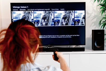 Benon, France - December 30, 2018: Woman holding a tv remote control In the process of selecting the viking success series proposed by Prime Video, a video-on-demand service created by Amazon.com