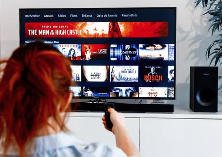 Benon, Francja - 30 grudnia 2018 r.: Kobieta trzymająca pilota telewizora przed ekranem wyświetlającym w języku francuskim stronę główną Prime Video, usługi wideo na żądanie stworzonej przez Amazon.com Publikacyjne