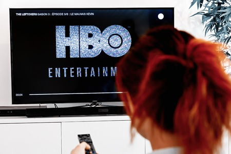 Benon, France - December 30, 2018: Woman watching tv serie produced by HBO which we see logo at the show begening. HBO is an American multinational entertainment company part of the WarnerMedia group Éditoriale