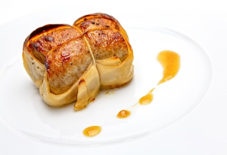 Paupiettes of veal put on a white plate with sauce on the side. Gourmet dish of French tradtion