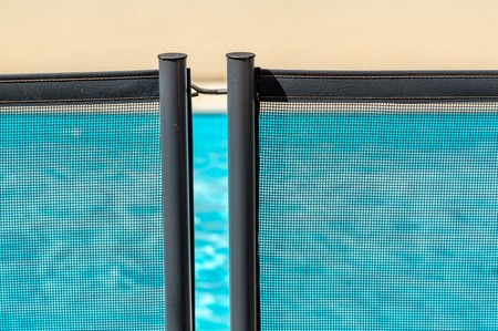 View of a pool through a mandatory safety net on the edges of a private psicine