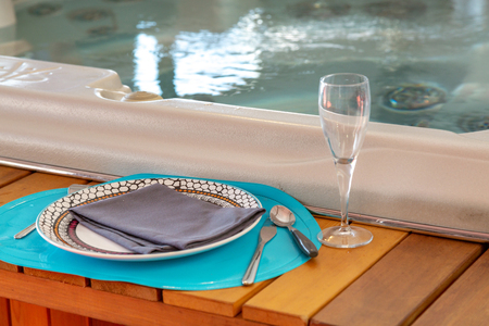 closeup on wooden frame around a jacuzzi with flatware for luxurious diners