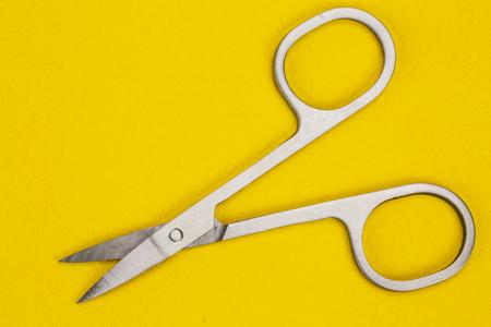 new sewing scissors on a yellow background Фото со стока