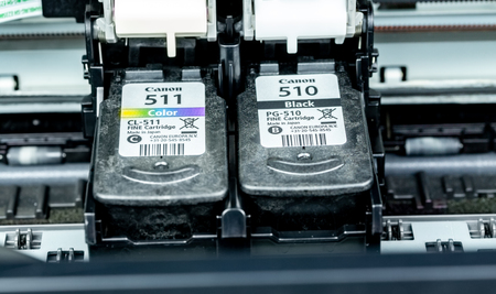 Benon, France - January 15, 2019: close up on Canon 511 (Color) and 510 (Black) inkjet cartridges In the printers ink compartment. Sajtókép