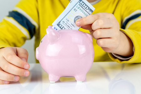 Seven years old boy puts dollars banknotes in a piggy bank, savings family concept