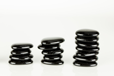 Three piles of zen pebbles on white background