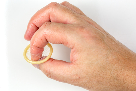Mans finger holding an open condom on a white background