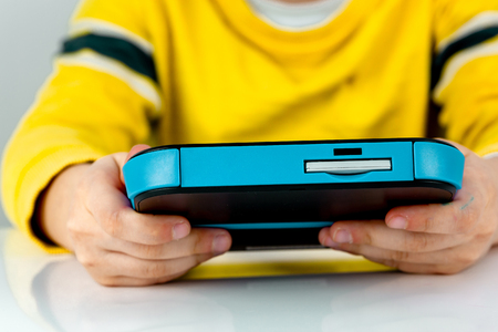 Young child playing on a game console on a white desk