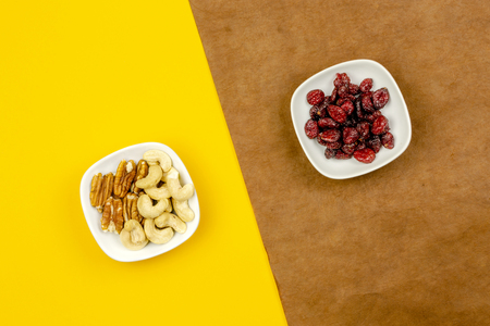 dry nuts and dry berries on bronwn and yellow background selective focus, top view