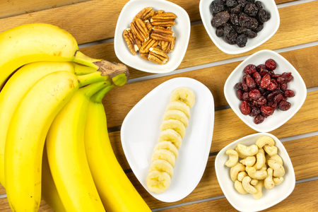 Vegan breakfast: variety of fruits, nuts and berries on the wooden table, selective focus, top view Stock Photo