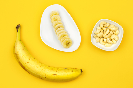 Raw Vegan breakfast: banana, nuts and berries on yellow background