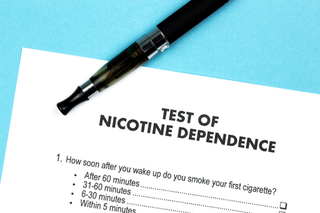 Test of Nicotine Dependence with e-cigarette on blue background