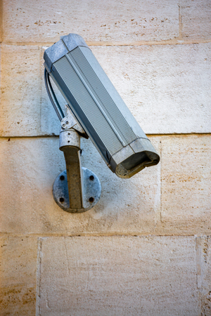 Close-up off old system CCTV camera mounted on a wall